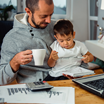 Father working from home with his son on his lap