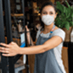 Happy business owner opening the door at a cafe wearing a facemask to avoid the spread of coronavirus