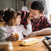 Toddler feeding bread to her father as they have breakfast