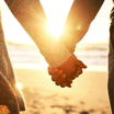 Upclose rearview shot of a young couple holding hands at the beach