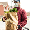 Mature man wearing protection mask, unloading grocery from car trunk